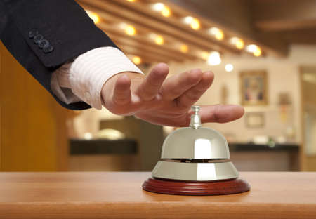 call bell: Hand of a businessman using a hotel bell