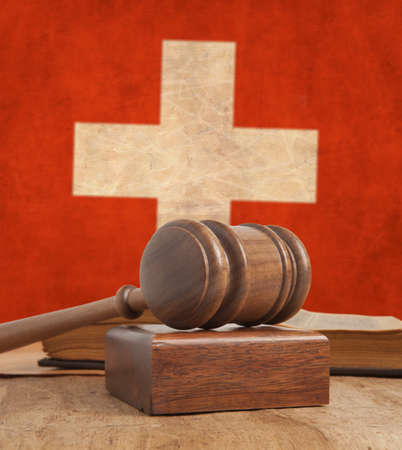 Wooden gavel and vintage Swiss flag  photo