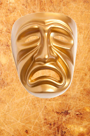 histrionics: Tragedy theatrical mask on a vintage texture background Stock Photo