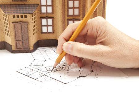Vrouwelijke architect hand en huis model