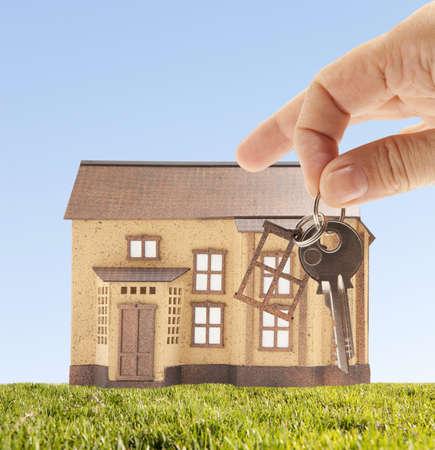 economic rent: Handing keys in the house sky background