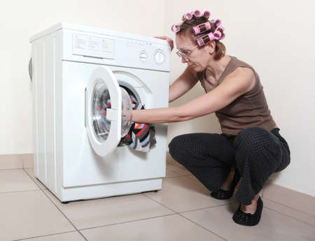 bending over: The woman with hair curlers adds garment to washing machine