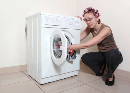 adds: The woman with hair curlers adds garment to washing machine
