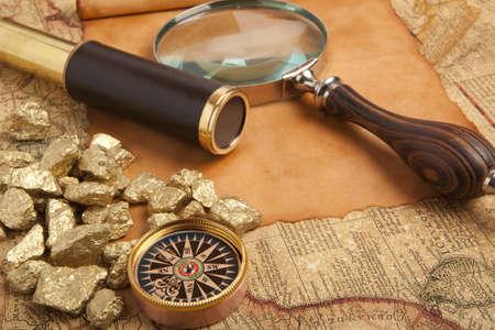 Goudklompjes en vintage koperen telescoop op antieke kaart