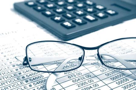 contabilidad: Gafas y calculadora en tabla de papel con el informe financiero Foto de archivo