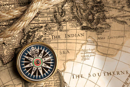 antiquity: Old compass and rope on vintage map