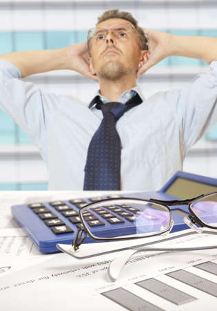 Accountant at desk in shirt and tie holding his head photo