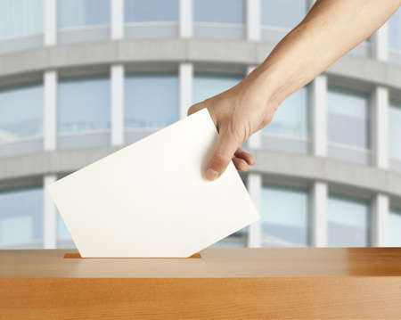 elect: Hand putting a voting ballot in a slot of box