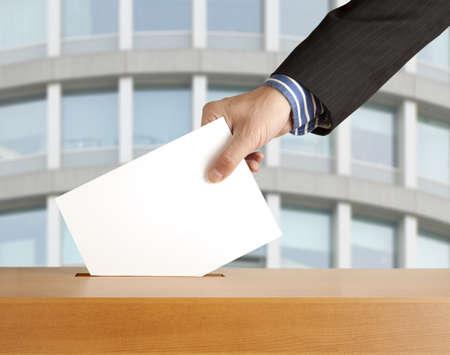 Hand zetten een stembiljet in een sleuf van de doos Stockfoto