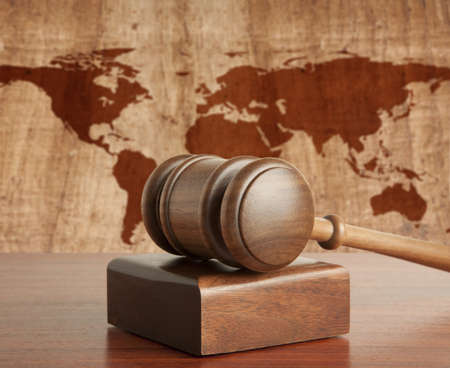 adjournment: Wooden gavel on a background map of the world