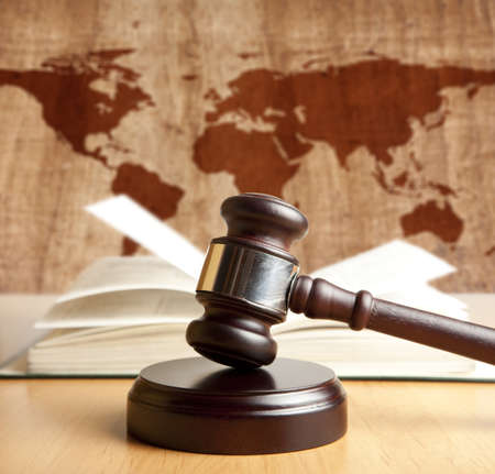 adjourned: Wooden gavel on a background map of the world