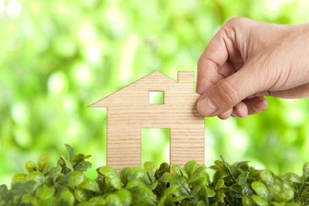 residential building insurance: Wooden model house in green field