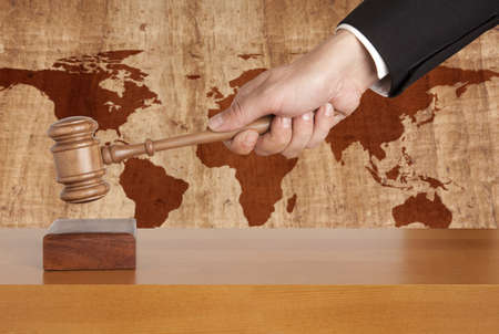 legally: Wooden gavel on a background map of the world