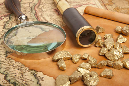 gold bullion: Gold nuggets and vintage brass telescope on antique map