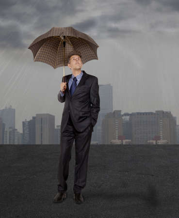 Businessman with umbrella standing in the rain  photo