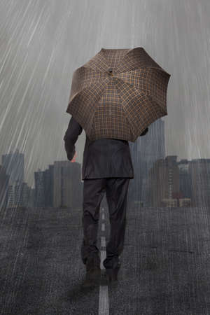 Businessman with umbrella walks in the rain  photo