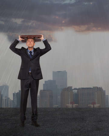 Businessman with briefcase standing in the rain  photo