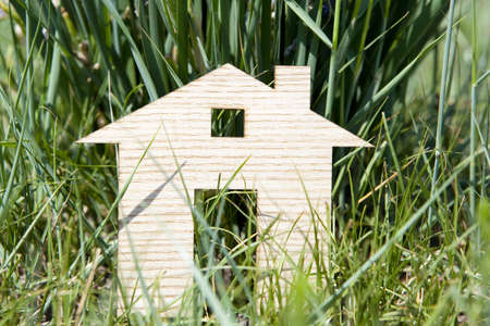 Wooden model house in green field photo