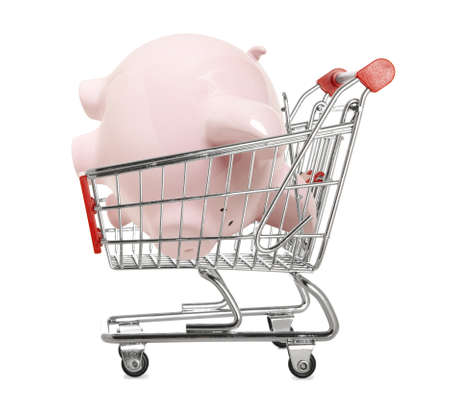 Piggy bank in a shopping trolley isolated on white  photo