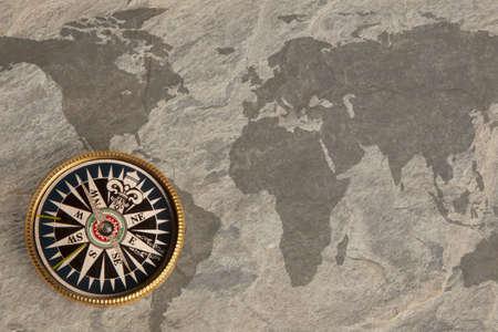 bygone: Old golden compass on vintage map Stock Photo