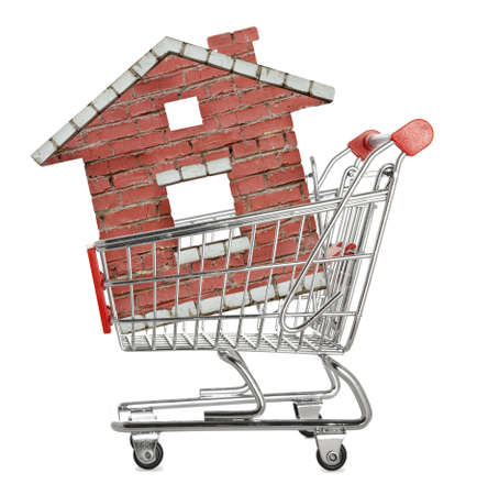 House concept - model of the house in shopping cart on white background  photo