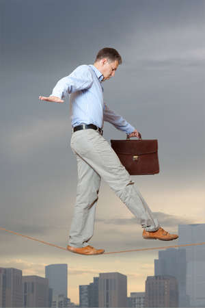 inconstant: Businessman in equilibrium on a rope over a cityscape Stock Photo