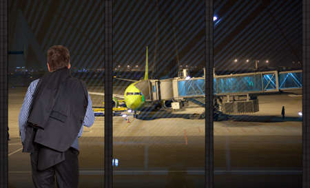 businessman standing in front of large glass windows looking at an airplane photo