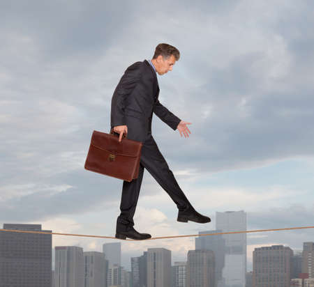 precipitate: Businessman in equilibrium on a rope over a cityscape Stock Photo
