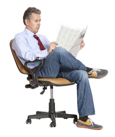 Businessman sitting in a chair reading a newspaper photo