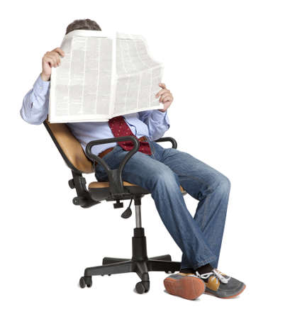 Homme d'affaires assis sur une chaise en lisant un journal Banque d'images