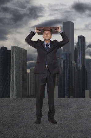 Businessman hiding from the rain on the background of skyscrapers Stock Photo - 20618872