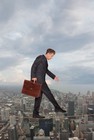 risky business: Businessman keeping his balance on a rope over a big city  Stock Photo