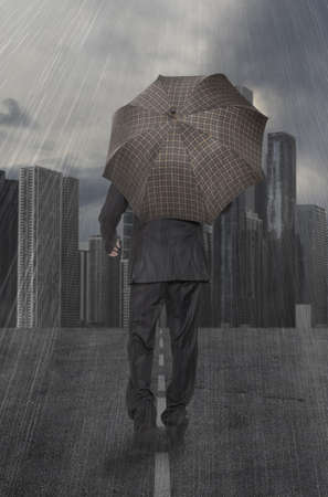 Businessman with umbrella walks in the rain on the background of skyscrapers photo