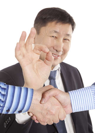 Business handshake between two colleagues on the background of asian businessman   photo