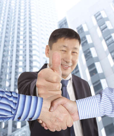 Business handshake between two colleagues on the background of happy asian businessman   photo
