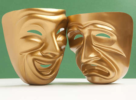 histrionics: Comedy  and Tragedy theatrical mask on a green background Stock Photo