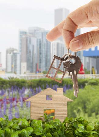 garden key: Wooden model house in green field on the background of skyscrapers