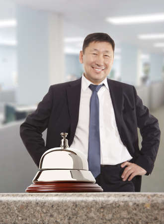 hotel receptionist: Asian hotel concierge.  Service bell at the hotel