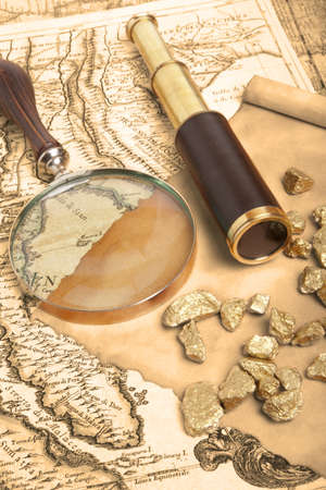 nuggets: Gold nuggets and vintage brass telescope on antique map