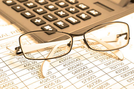 Glasses and calculator on paper table with finance report. Sepia color photo