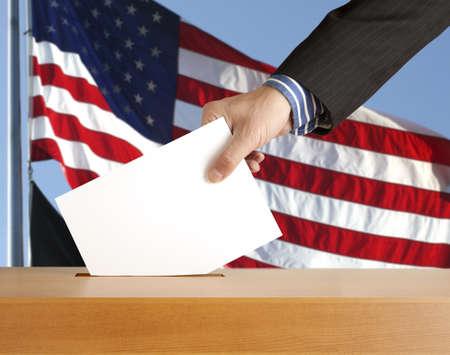 Hand with ballot and box on Flag of USA photo