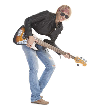Woman with long legs playing guitar, wearing torn blue jeans and sunglasses, standing, looking at camera. Isolated on white photo