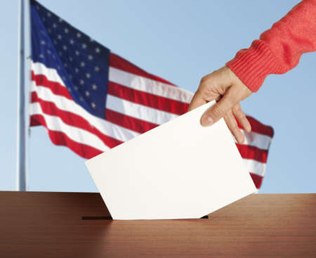 ballot papers: Female hand with ballot and box on Flag of USA