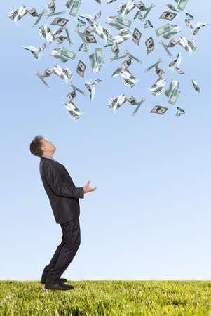 uomo sotto la pioggia: Uomo d'affari sorpreso e volare banconote in dollari contro il cielo blu