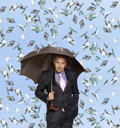 Happy businessman man with umbrella and flying dollar banknotes against blue sky  photo
