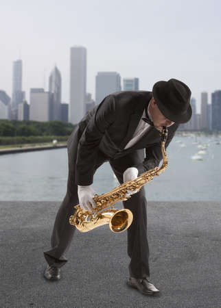Saxophonist. Middle aged man playing on saxophone against the background of skyscraper photo
