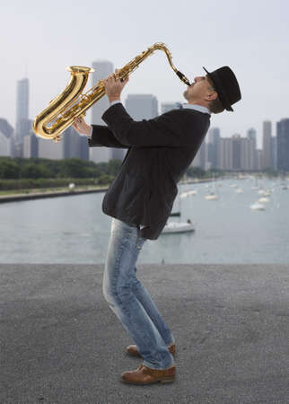 Saxofonist. Man van middelbare leeftijd spelen op saxofoon tegen de achtergrond van de wolkenkrabber
