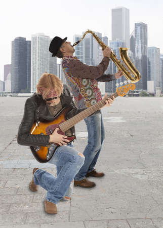 The duo of musicians with guitar and saxophone against the background of skyscraper Stock Photo - 21139700