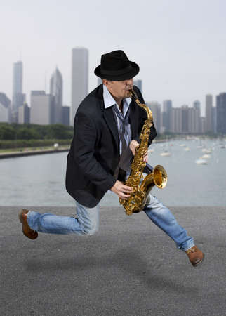 Saxophonist. Middle aged man playing on saxophone against the background of skyscraper Stock Photo - 21139701