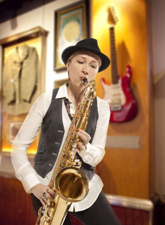 hard rock: Saxophonist. Middle aged woman playing on saxophone against the background of rock cafe Stock Photo